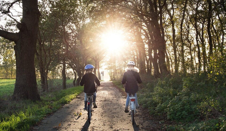 An image of two children riding their bikes on a path through green trees.